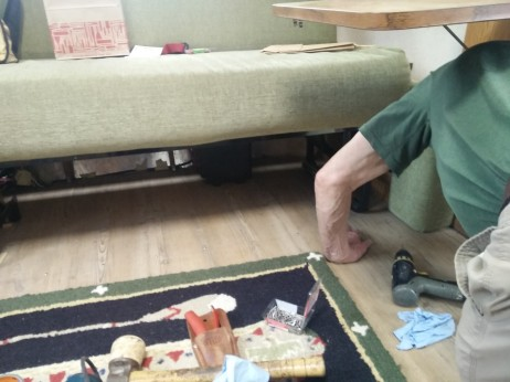 Jim tapped the flooring back in place from underneath the sofa